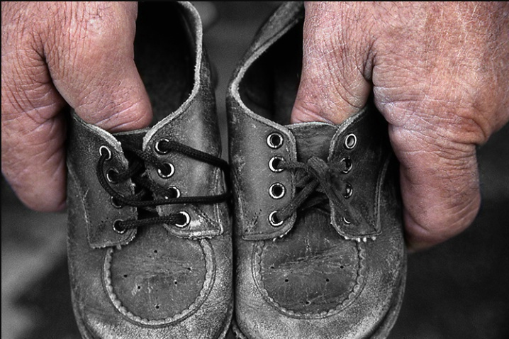 Dad Holding Baby Shoes